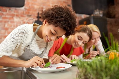 happy women cooking and decorating dishes